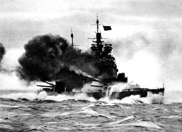 Photograph showing the Royal Navy battleship HMS 'Duke of York' firing her 14-inch guns, whilst heavy seas break over her bows, sometime during the Second World War