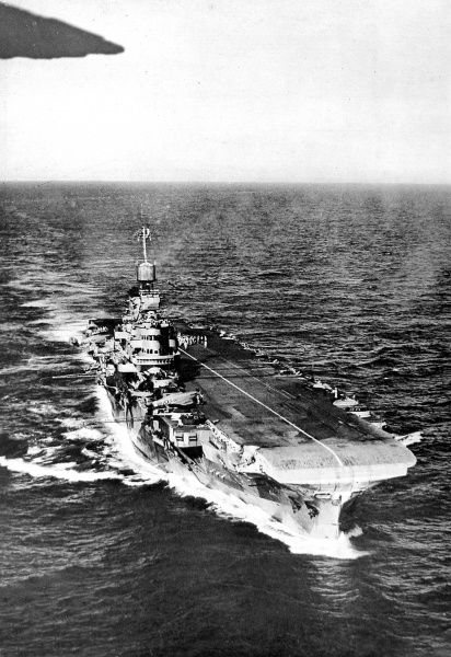 Aerial photograph of the Royal Navy aircraft-carrier HMS 'Indomitable' under way, 1945. A 'Seafire' fighter airplane is visible, parked on her foredeck
