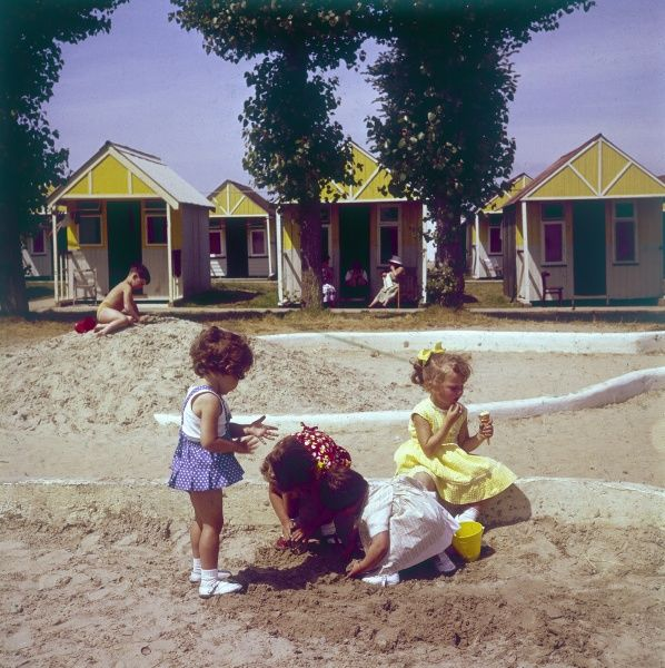 Children playing in the sand on the beach in front of a row of yellow chalets at a British holiday camp. Date: 1960s