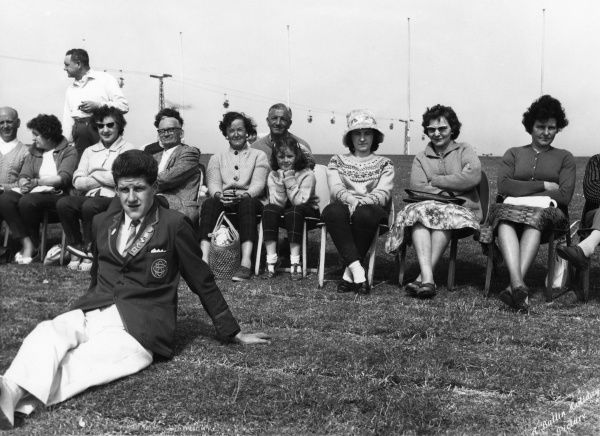 A group of adults sitting in a row, with one little girl in the middle, and a male Redcoat sitting on the grass in the foreground, at Butlin's holiday camp, Filey, North Yorkshire. (1 of 2) Date: circa 1962