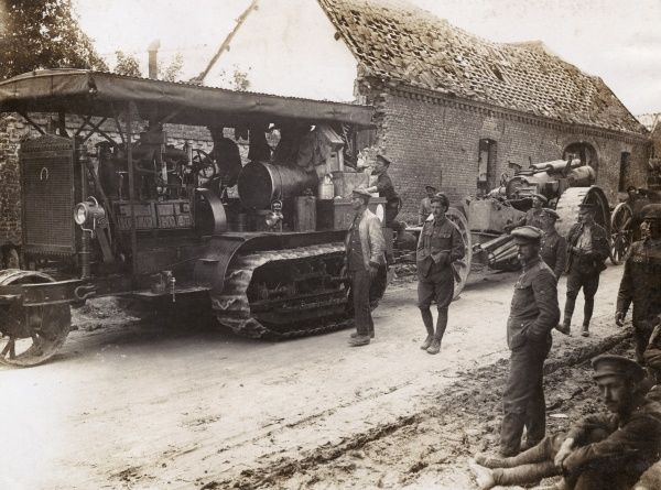 A Holt tractor transporting heavy artillery (probably a Howitzer) along a country road during the First World War. Date: 1914-1918