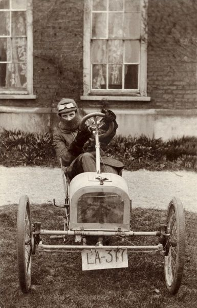A young man got up in motoring kit including a balaclava and goggles, poses at the wheel of an evidently home made car with hand-scrawled number plate!