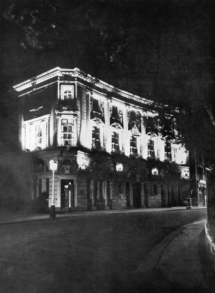 The lower part of Ingram House, in the Strand, just opposite the bombed-out shell of St. Clement Dane's Church, as it is illuminated after nightfall