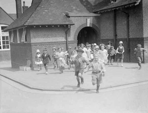 School's out! A group of joyous, smiling schoolchildren, running out of their school at the end of the day. Date: 1930s