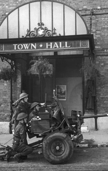 British soldiers outside a town hall with a rapid fire anti-tank unit ready for action on the Home Front in England during World War II