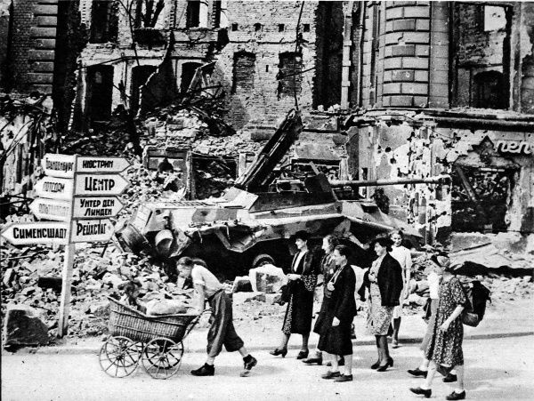 Photograph showing a group of Berliners walking past the ruins of Nollendorf Platz looking for a place to live, after the end of the Second World War, Summer 1945. In the background a wrecked German tank and a Russian street sign sit side by side