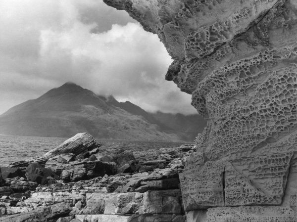 Rocks honeycombed by the sea, with Garsbheinn, one of the Coolin Peaks, in the background. Port na Cullaidh, Loch Scavaig, Elgol, Isle of Skye, Scotland. Date: 1950s