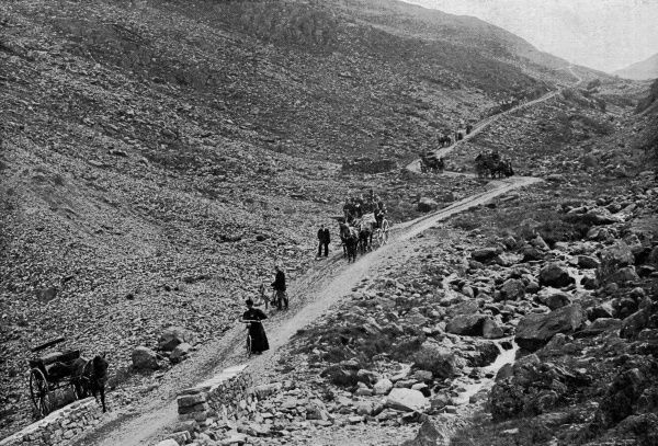 Cyclists and horse-drawn carts descending Honister Pass, Cumbria Date: 1890s