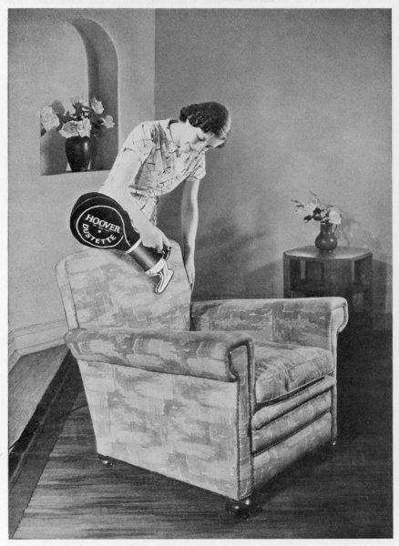 "A housewife demonstrates how to vacuum clean an armchair using a Hoover ""Dustette"" cleaner"