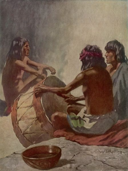 Three men of the Hopi tribe of the Pueblo people of New Mexico sing their traditional religious songs accompanied by a drum, in the kiva building which women may not enter