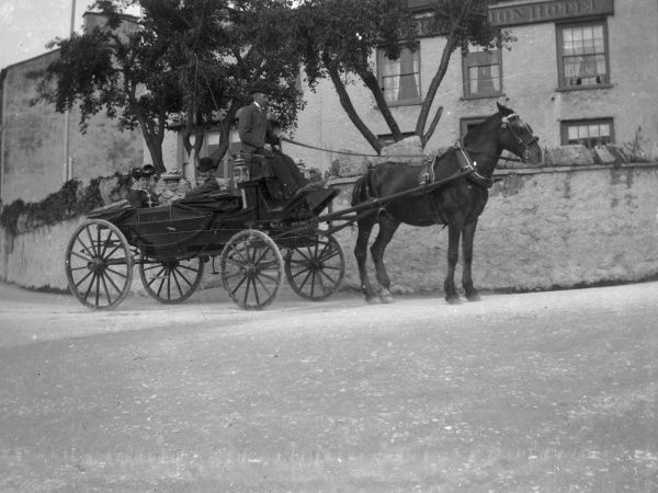 A horse and open carriage with rider and three passengers outside the Albion Hotel in St Davids, Pembrokeshire, Dyfed, South Wales