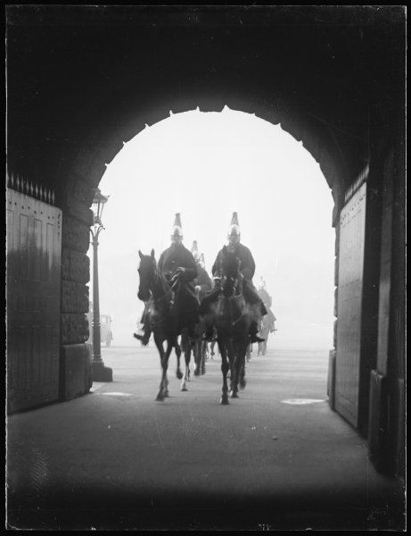 Two royal horse guards riding under an archway at Whitehall, London, probably arriving to take part in the Trooping of the Colour parade