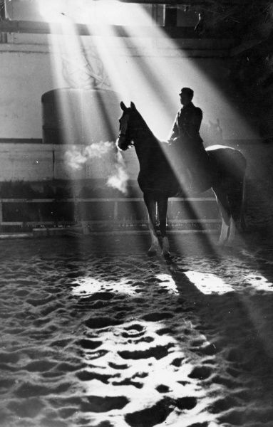 A study of a horse and rider, rays of sunlight streaming through a window, highlighting the steam coming from the horses' nostrils. Date: 1930s