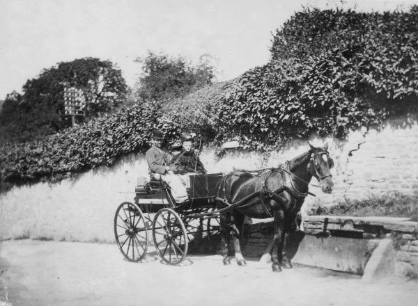 A horse drawn trap with two passengers outside Crickhowell Castle wall, Crickhowell, Powys, Mid Wales