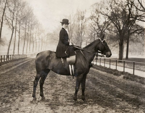 A smartly dressed horsewoman riding sidesaddle poses for her photograph in a misty landscape