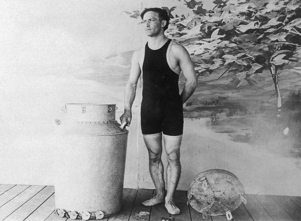 Harry Houdini with a canister from which he emerged while underwater