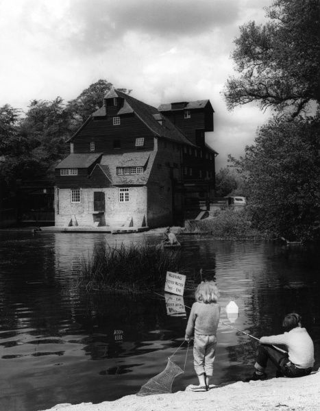 Children fishing in the River Ouse, beside Houghton Mill, a large 18th century timber water mill, near Huntingdon, Cambridgeshire, England. (A Youth Hostel at the time). Date: 18th century