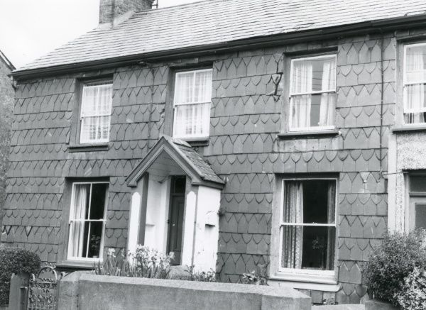 View of the front of a house with decorative slate tiling, somewhere in North Wales. The house is double-fronted, but appears to be either terraced or semi-detached