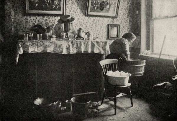 The interior of a house in the East End of London. A woman has her hands in a wooden wash tub and further buckets are on the floor nearby