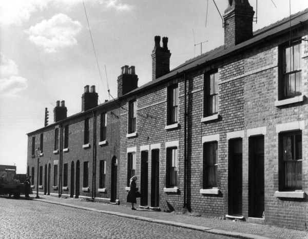 A woman waits outside a terraced house on a cobbled street in Warrington, Cheshire Date: circa 1960