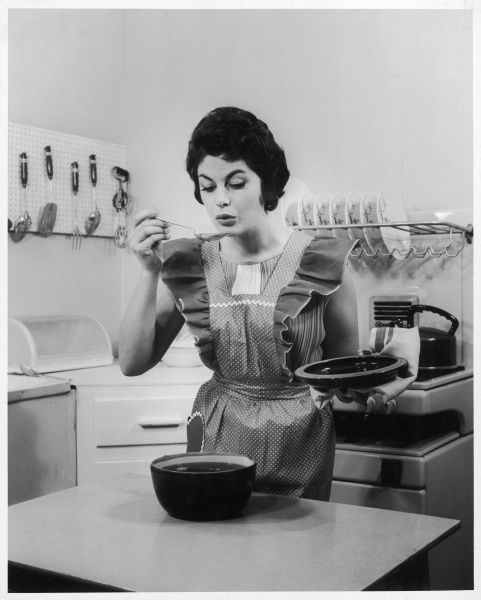 A housewife tastes one of her creations with a spoon, wearing a frilly apron, and standing in an immaculate kitchen