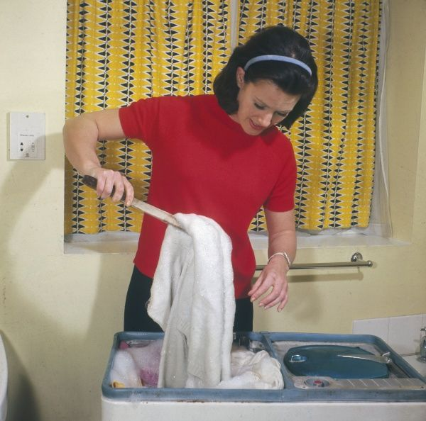 A young housewife uses wooden pincers to pull her laundry out of the 'washing' half of the 'Twin Tub' washing machine to put it into the 'spinning' half