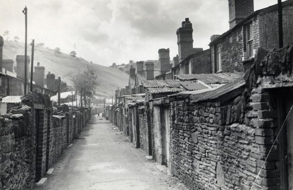 A view along an alley between back to back terraced housing in Llanhilleth, Blaenau Gwent, South Wales, showing walls made of a mixture of brick and stone, and ramshackle corrugated iron roofing