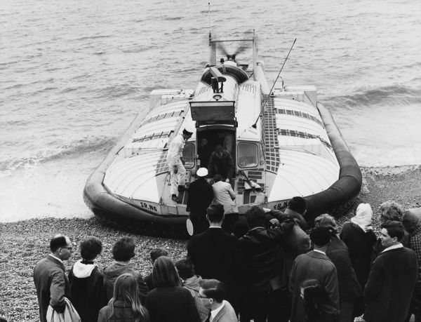 Passengers waiting on an unspecified British beach for others to disembark from a hovercraft so that they can get on. Date: 1960s