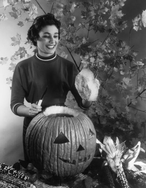 A happy housewife cuts the lid into the top of her huge Halloween (or Thanksgiving) pumpkin lantern! Date: 1960s