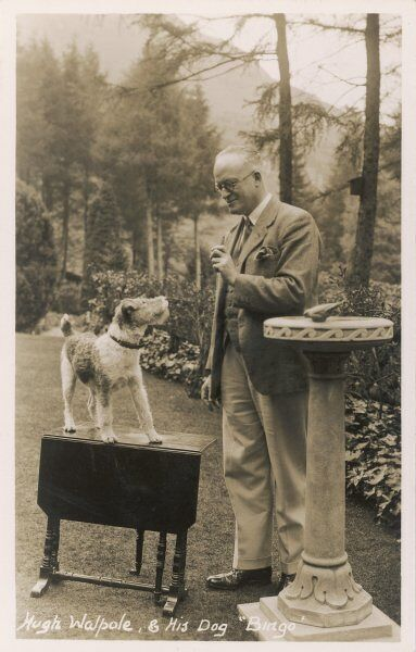 The popular novelist Hugh Walpole and his wire-haired fox terrier Bingo, in the garden of their home at Keswick, Cumbria