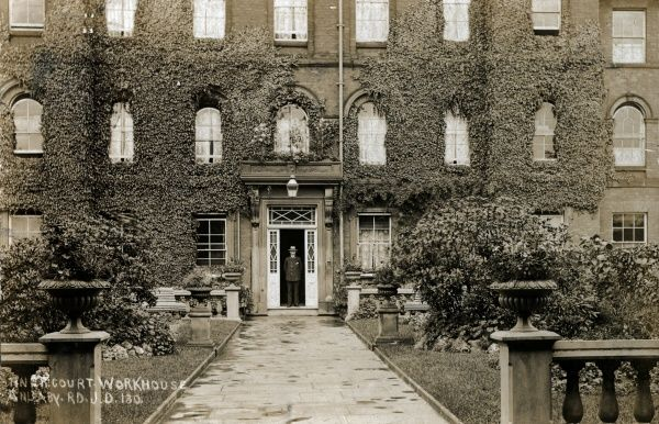 The entrance to the main building of what was formally known as the Kingston-upon-Hull Incorporation workhouse, Yorkshire. The workhouse master stands at the door. The workhouse, opened in 1852 on Anlaby Road, Hull, was designed by Henry F Lockwood