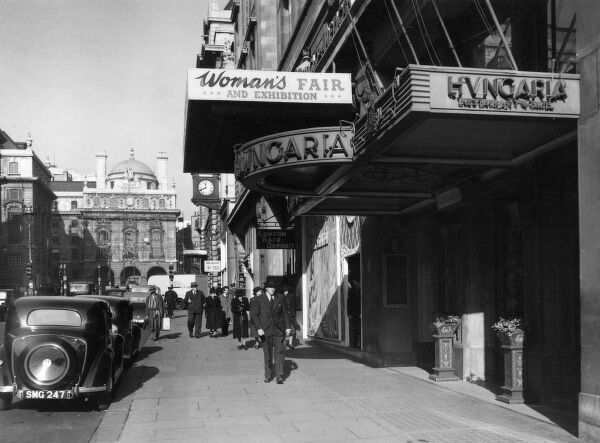 Exterior of the Hungaria Restaurant, Regent Street, London, 1947. A prominent sign next door advertises the Woman's Fair and Exhibition. Date: 1947