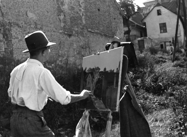 An old, dilapidated part of Budapest, Hungary, is a source of interest to this artist at his easel. Date: 1930s