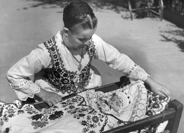 A young mother in traditional embroidered costume, tucking her baby into its cot, covered in traditional embroidered bedclothes, Talma, Hungary. Date: 1930s