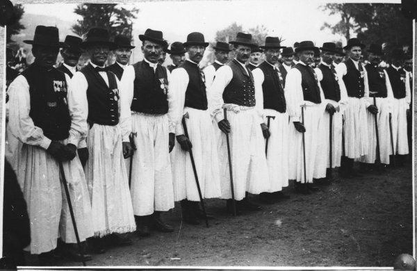A proud line-up of Hungarian peasant men, war veterans, wearing their medals with their traditional costumes