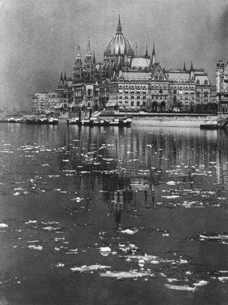 The Houses of Parliament reflected in the icy waters of the River Danube, Budapest, Hungary. Date: 1930s