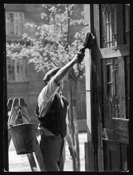 A window cleaner in Budapest, Hungary, who also washes down doors
