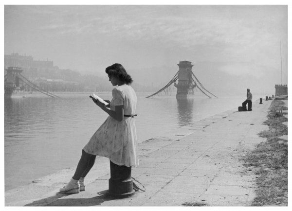 A young woman reading on the banks of the River Danube, next to the Elizabeth (Erzsebet) Suspension Bridge destroyed during World War Two, Budapest, Hungary
