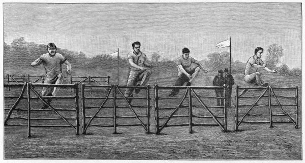 Four hurdlers clear the hurdles almost simultaneously