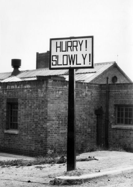 Hurry! Slowly! This curiously worded signpost is to be seen by the roadside near Ashby-de-la-Zouche, Leicestershire, England. It warns of a open Level Crossing Date: 1950s