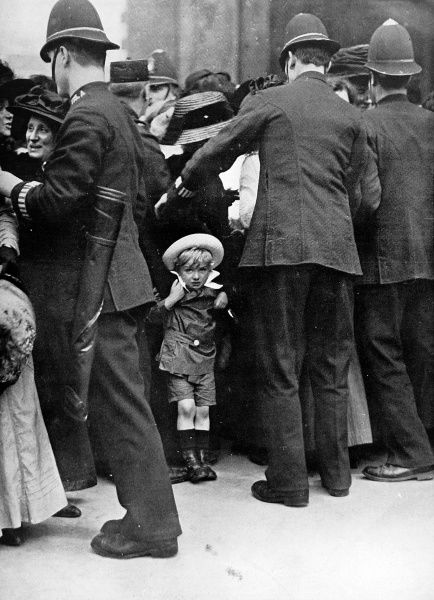 A photographic study entitled, ' I want to go home, mother.' A small child pictured at the edge of a large crowd being held back by the police