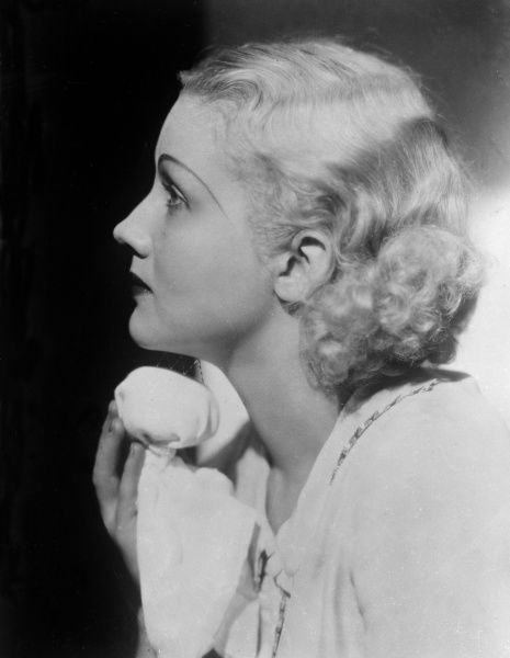 This glamorous platinum blonde model demonstrates how to do a facial massage with a block of ice wrapped in a flannel. Date: early 1930s