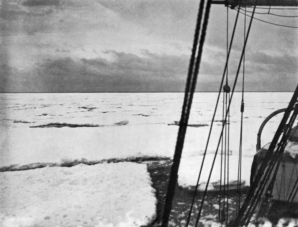Shackleton's ship 'Nimrod' pushes through heavy floes in the Ross Sea. The dark line on the horizon is a 'water- sky' and indicates the existence of the open sea. Date: circa 1907