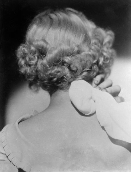 A platinum blonde model demonstrates how to relieve stress and tension by applying ice wrapped in a flannel to the back of the neck. Date: early 1930s