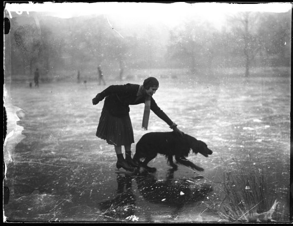 An ice skating dog out with his young mistress at Wimbledon Common, London, England
