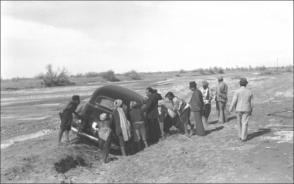 A large number of people trying to move a car out of a ditch, somewhere in Iran