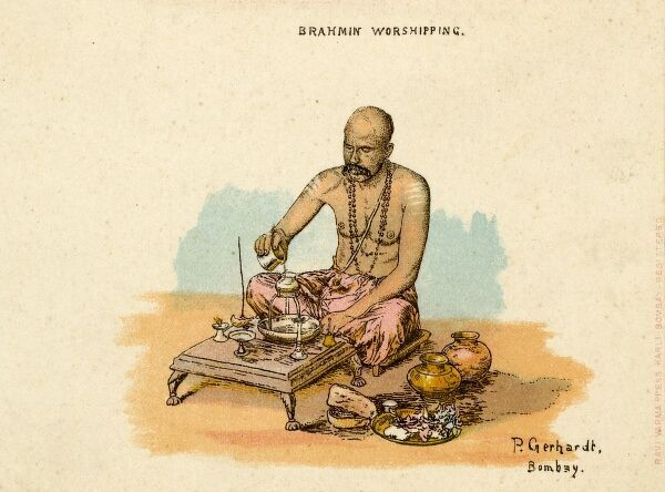 A Brahmin worshipping in India. He is sitting cross-legged making an offering at a low table