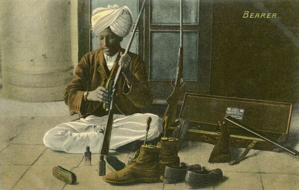 Indian 'Bearer' - cleaning his Master's shoes and guns prior to heading out on a hunt