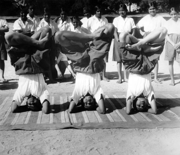 What may look like headstands is really a position of penitence. These Indian girls are copying the position of the holy ascetics (Saddhus), who sit like this for hours. Date: 1930s
