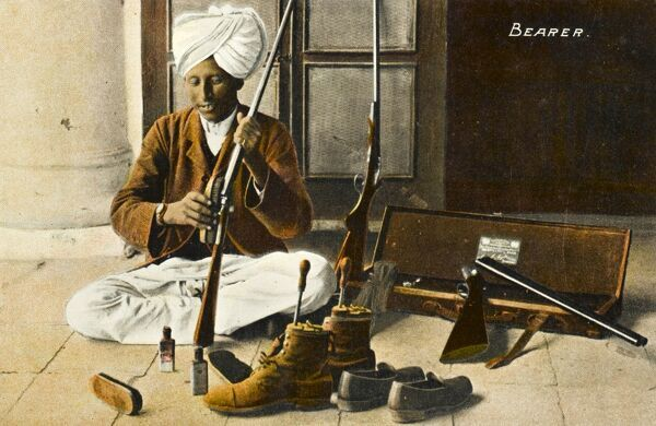 Indian servant sitting cross-legged, cleaning his Master's equipment, including his boots and shoes and hunting rifles with brushes and polish